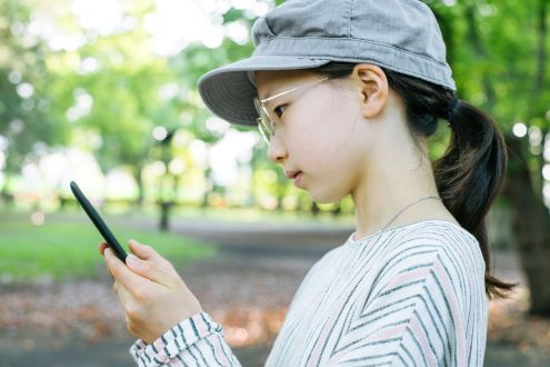 A girl uses her smartphone to measure silence.