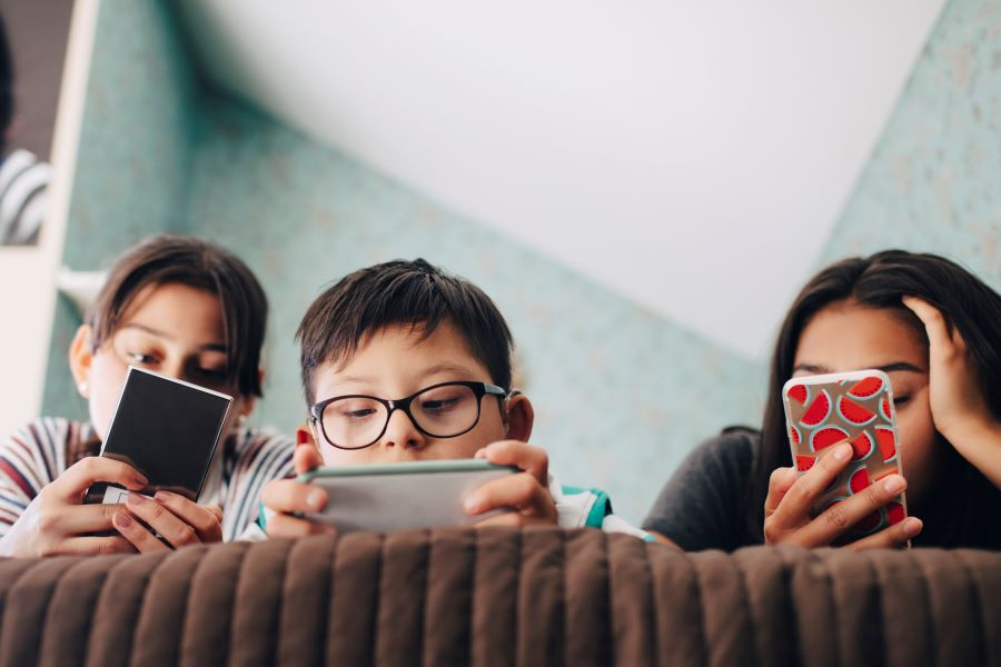 Three children looking at their phones